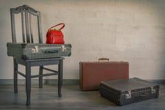 Gamla resväskor och röd påse Arkivfoton