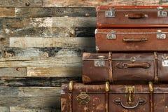 Gamla resväskor på träbakgrund Arkivfoto