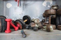 Gamla retro hantlar ligger på golvet i en boxningidrottshall, sportkugghjulet, utrymme för text royaltyfria foton