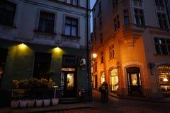 Gamla Riga på natten, Lettland, Europa - folk som går i historiska gator av den europeiska huvudstaden royaltyfri bild