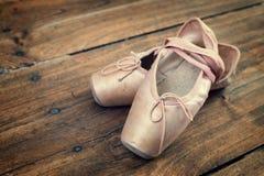Gamla rosa balettskor på ett trägolv Royaltyfri Bild