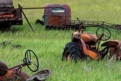 Gamla rostade traktorer i grönt gräs för fält royaltyfri bild