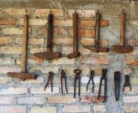 Gamla rostiga arbetshjälpmedel hängde på en tegelstenvägg En rad av hammare av det olika formatet och en rad av forntida plattång Royaltyfri Foto