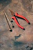 Gamla rostiga brutna hjälpmedel, spikar och plattång på en bakgrund av rost Royaltyfri Fotografi