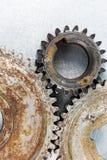 Gamla rostiga mekaniska kugghjul på skrapad metallbakgrund, Arkivfoto