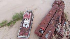 Gamla rostiga skepp på flodstranden på sanden Flyg- filmande arkivfilmer