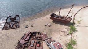 Gamla rostiga skepp p? flodstranden p? sanden Flyg- filmande stock video