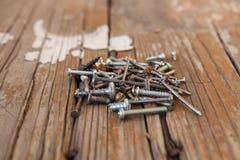 Gamla rostiga skruvbultar på den wood texturcloseupen Arkivfoto