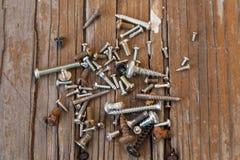 Gamla rostiga skruvbultar på den wood texturcloseupen Royaltyfria Foton