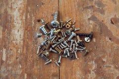 Gamla rostiga skruvbultar på den wood texturcloseupen Royaltyfri Bild