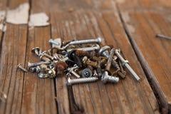 Gamla rostiga skruvbultar på den wood texturcloseupen Royaltyfri Fotografi