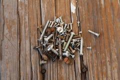 Gamla rostiga skruvbultar på den wood texturcloseupen Arkivbilder