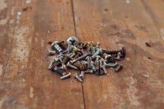 Gamla rostiga skruvbultar på den wood texturcloseupen Royaltyfri Foto