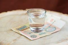 Gamla 10 rubel ussr på tabellen under ett exponeringsglas av vodka, röd bakgrund Royaltyfri Fotografi
