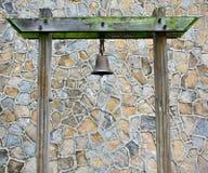 Gamla Rusty Bronze Metal Bell Hanged på en grön mossig träpelare i en stenmodellvägg arkivbild