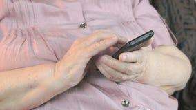 Gamla rynkiga händer som rymmer mobiltelefonen close upp stock video