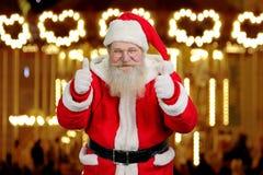Gamla Santa Claus som ger upp tummar med båda händer Royaltyfria Foton