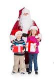 Gamla Santa Claus som kramar pysen och flickan med gåvor. Arkivbilder
