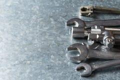 Gamla skiftnyckel och hjälpmedel och motorreservdelar royaltyfria bilder