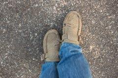 Gamla skor med jeans på bakgrunden av cementet fotografering för bildbyråer