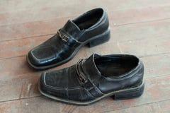 Gamla skor på det smutsiga golvet Royaltyfri Foto
