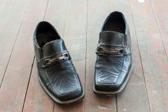 Gamla skor på det smutsiga golvet Arkivbilder