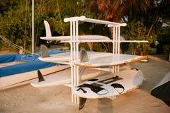 Gamla skrapade och skadade surfingbrädor på en kugge står för reparation på stranden Royaltyfria Foton