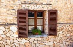 Gamla slutarefönster med en kruka av blommor. Mallorca. Mediterrane Royaltyfria Foton