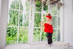 Gamla små roliga två år behandla som ett barn flickan i stilfull röd kläder, och jeans och gymnastikskor står med baksida på föns royaltyfri foto