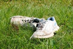 Gamla smutsiga sportskor på gräs Arkivfoto