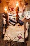 Gamla snirklar och stearinljus är den gamla scribe'sens arbetsplats Arkivfoton