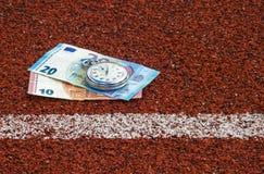 Gamla sportstoppur och pengar på rinnande spårgummi royaltyfri foto