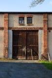 Gamla stängda rustigladugårdportar i vägg för röd tegelsten Lantlig dörr i solnedgångljus Arkivfoto