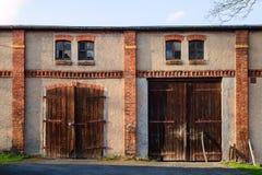Gamla stängda rustigladugårdportar i vägg för röd tegelsten Lantlig dörr i solnedgångljus Royaltyfri Fotografi