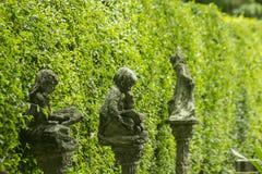Gamla statyer i trädgården arkivbilder