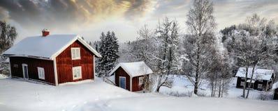Gamla stugor i ett snöig vinterlandskap Royaltyfri Bild