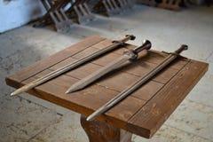Gamla svärd på trätabellen Royaltyfri Bild