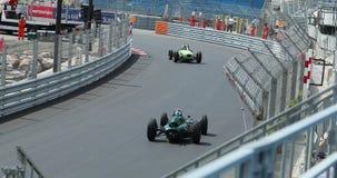Gamla tävlings- bilar som rusar längs kurvan