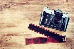 Gamla tappningkamera- och filmremsor över träbrun bakgrund Royaltyfri Foto