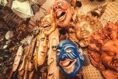 Gamla teater- och souverirmaskeringar i lager med tappningkonstobjekt och antikviteter Arkivfoto