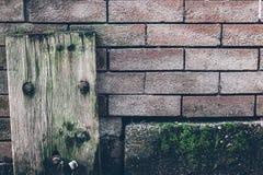 Gamla texturer av trä- och tegelstenväggen med mossa royaltyfria bilder