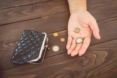 Gamla tomma plånbok och mynt i händerna Tomma handväska och mynt för tappning i händer av kvinnor Armodbegrepp konkurs royaltyfria bilder
