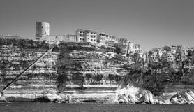 Gamla torn och hus på stenig kust i Bonifacio Arkivbilder