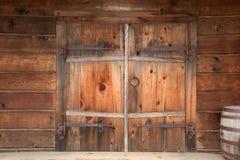 Gamla trädubbla dörrar med rostig riden ut maskinvara, royaltyfria bilder