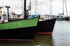 Gamla träfiskebåtar förtöjde i hamnen av Volendam arkivfoto