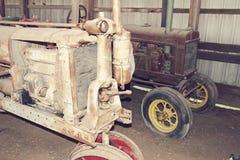 Gamla traktorer i en ladugård Royaltyfri Foto