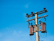 Gamla transformatorer på konkret pol med blå himmel Royaltyfri Bild