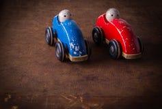 Gamla två, enkla, naturliga, trä- skadade leksakbilar med dockor Fotografering för Bildbyråer