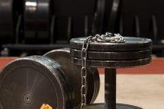 Gamla två och använda hantlar för idrottshallsvartmetall med silverkedjan Idrottshallutrustning arkivfoton