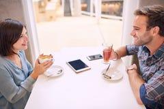 Gamla vänner som har en bra konversation i modernt kafé Royaltyfria Bilder